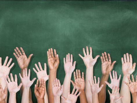 Diverse raised hands in front of blackboard
